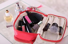 czerwona kosmetyczka z kosmetykami do makijażu na szklanym stole